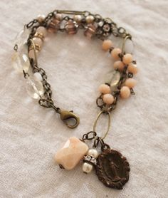 triple-strand bracelet is a mix of cut glass rose beads, vintage pearls, an oversized Peach Aventurine bead, faceted chuncky Citrine, faceted Pineapple Quartz ovals, Peach Aventurine rounds, a vintage Miraculous Medal of Mary and wonderful old rhinestone rondelles.