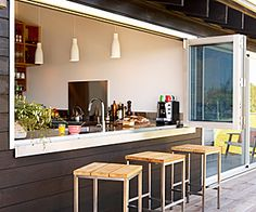 A hip modern beach house in Copacabana boasts a completely indoor-outdoor kitchen  dining set up.