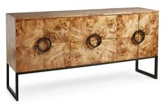 "Jagger 72"" Sideboard, Burled Wood. This sideboard modernizes a classic look with contemporary appeal. Atop sleek legs, clean-lined doors with geometric pulls conceal practical storage. Made of: frame, burl veneer/maple solids; base, stainless steel; hardware, stainless steel. Size: 72""W x 18""D x 35""H Color: frame, copper/gold; hardware, gunmetal. $3,299.00"