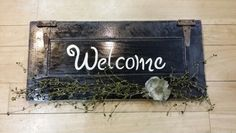 Welcome sign on an old cupboard door.  Added old hinges and green berry garland