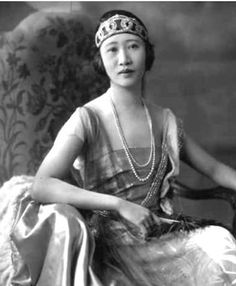 Huang Huilan (1893-1993), married to the renowned Chinese diplomat Wellington Koo, made her name in the western world as Madame Wellington Koo or Hui-lan Koo for her adaptations of traditional Manchu fashion, which she wore with lace trousers and jade necklaces.