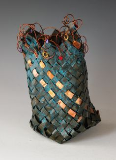 """Bias plaited copper basket ,with a blue green patina- colourful aluminum discs, washers & wire have been added to the rim. Heat coloured copper strips were woven in for accent. 10"""" x 6.5"""""""