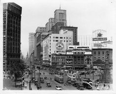 Campus Martius. The Majestic Building, Central United Methodist Church, the David Broderick Tower, Hudson's, Sallan Jewelers, Kern's, Golde Clothing, the Detroit Opera House, Roesink's Clothes, United Shirt Distributors, Randall Clothes, the Bagley Memorial Fountain, and the Michigan Soldiers' and Sailors' Monument are all pictured. Advertisements are posted for Red Crown Gasoline, the Wayne County Democratic Committee's endorsements for the 1928
