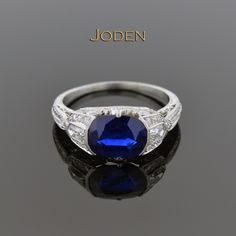 A beautifully cut oval sapphire sits east-west in this gorgeous Art Deco diamond ring. The sapphire has a weight of 2.50 carats with a color of blue and moderately to heavily included. Flanking the center are two bullet cut diamonds that have a weight of approximately .30 carat total weight. Accenting the ring are 32 single cut diamonds that have a weight of approximately .32 carat total weight.