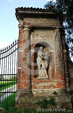 Photo taken to the column that supports the gate of a Palladian villa located along the main road connecting Padua to Vicenza in Veneto (Italy). shooting from the road in the image you see, within a niche of the large pillar built of brick red color, a statue of a woman.