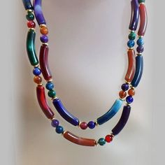 This #vintage marbled Lucite necklace is gorgeous!  It features a two strand heavy Lucite bead necklace with marbled red, gold, green and blue curved long tube beads alterna... #ecochic #etsy #jewelry #jewellery