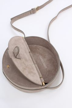 """Round cross-body bag in 100% suede leather. Magnetic closure and adjustable strap. Available in grey or melon. 7.75"""" x 7.75"""" x 2"""""""