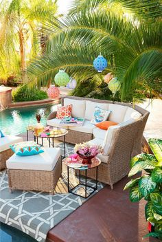 Colorful lanterns, tropical plants, a beautiful pool,  and pretty pops of color make this outdoor space the perfect staycation spot.