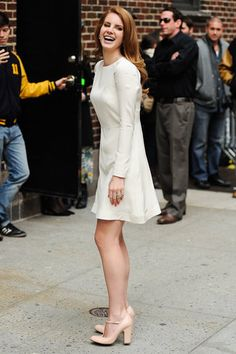 Lana Del Rey in a white dress and pale pink pumps.