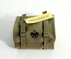"""Designed by Victoria Caswell   Country: United States  """"This sewing kit for boy scouts meant to resemble a sleeping bag. It is made out of a oliver green canvas, and is adorn with pulls and snaps to give the idea of general camping equipment and rolls up and unrolls like a sleeping bag."""""""