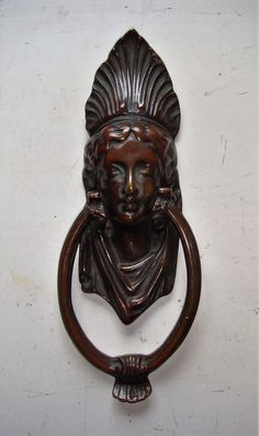 Genuine Edwardian Egyptian Queen or Greek Goddess Brass Door Knocker. I can't quite decide who she is, all I know is that she seems to give an aura of peace and calm, in addition to which she has a great patina only achieved with age. Complete with original brass striking plate and new fixing studs. Slim in width and ideal for glazed doors with a narrow centre stile.