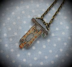 Cute ginger tabby cat hanging from tree branch hand-drawn shrink plastic pendant necklace. £8.00, via Etsy.