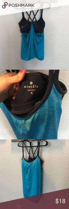 Athleta tank with attached bra EUC Cute Athleta tank with criss cross back straps and swooping sides. It is teal with a navy bra which has removable padding. Light and airy fabric. I believe I wore this one time, no visible signs of wear. Athleta Tops Tank Tops