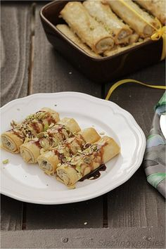 A new way to eat Baklava in Cigar form - topped with chocolate-caramel sauce and pistachios.
