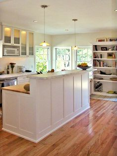 like the look of this kitchen. Great bookcase built in and beautiful windows in the corner. I also like how the cabinetry goes all the way to the floor. No way for crumbs and the like to get caught in corners underneath.