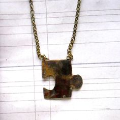 use a puzzle piece and a rusting medium to make a faux brass necklace