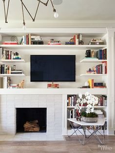 Style: Modern  The TV has space to breathe, as the wall above the fireplace extends across the firebox as well as an adjacent built-in bookcase. Shelves frame the TV, adding visual interetest around the screen so it isn't just a floating black box.  Informality and simplicity!