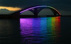 Xiying Rainbow Bridge - an elevated pedestrian walkway in Taiwan. The bridge is lined with a thin neon band that reflects a rainbow onto the water's surface below at night.