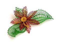 Ich habe hier eine Blume in Rot-Gelb-Grün geklöppelt. In der Mitte befinden sich Perlen und Pajetten. Auf der Rückseite befindet sich eine Ansteckn...