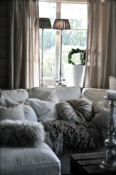 looks chic and cozy, loving the furry pillows and throw