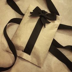 (A través de CASA REINAL) >>>>  Brown paper with black ribbon. Love the way the ribbon is attached