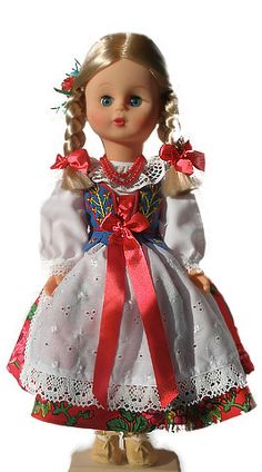 Strój Góralki Żywieckiej  strój kobiecy: spódnica w kwiaty, mocno marszczona, w różnych kolorach (czerwony, biały, zielony, szafirowy, czarny), fartuch biały z z białym haftem, biała koszula, gorset sznurowany z przodu wstążką, z charakterystycznym wyszyciami, na nogach kierpce, włosy splecione w jeden warkocz z kokardą. Pracownia Lalek Regionalnych FOLKLOR
