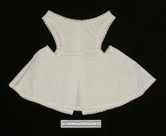 Pinafore, girl's, white cotton, small diamond weave, 1875-1885----White cotton, with small woven diamonds; sleeveless with straps slightly off the shoulder; cut of back and front identical, with one piece bodice and skirt; skirt flared out; deep armholes are open to waist and curve in towards stomach at waistline; back opening, closes with five white buttons in the bodice section; skirt, armholes and neckline are all finished off in a white embroidered eyelet lace.