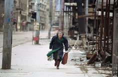 """On her way home in afternoon on Thursday, April 8, 1993 in Sarajevo, a Bosnian woman rushes down an empty sidewalk past war-destroyed shops in one of the worst sections of the so-called """"Sniper Alley."""""""