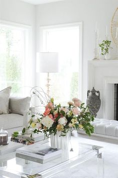 A lucite coffee table accented with coffee table books sits on a white rug in an elegant living room. Art Deco Coffee Table, Coffee Table Books, Blue Floral Wallpaper, Lucite Coffee Tables, Velvet Furniture, Blue Cushions, Elegant Living Room, Transitional Living Rooms, White Rooms