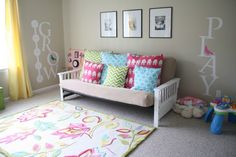 The bright colors in this #playroom just scream out for fun! #patternpillows #floralrug