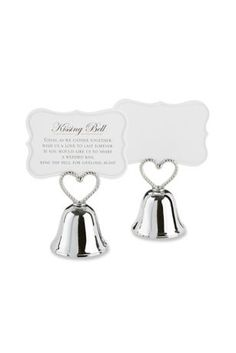 """Bells will ring joyfully on your wedding day, when a single kiss at the altar changes your life forever! Give your guests and yourselves the pleasure of reliving the moment over and over again with our """"Kissing Bell"""" Place Card/Photo Holder with a braided-heart handle. A sweet poem on the back of the place cards invites guests to """"ring"""" for a kiss from the happy couple. Start smooching!  Features and Facts:   Sweet, silver-finish metal bell place card/photo holder with braided, openwork"""
