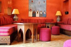 Moroccan style interior design, orange red colors, upholstered Moroccan poufs, wall art and Moroccan decorations for living room design. Moroccan Decor Living Room, Moroccan Room, Moroccan Theme, Moroccan Interiors, Moroccan Design, Moroccan Style, Living Room Decor, Moroccan Lounge, Moroccan Colors