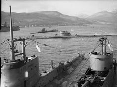 JUL 18 1942 HMS Unbroken navigates a minefield HMS GRAPH (ex U-Boat U 570) at Holy Loch on the completion of a trial trip, passing by a depot ship. In the foreground are the conning towers of HMS STURGEON (left) and HMS TIGRIS whilst submarine P 42 (later renamed HMS UNBROKEN) can be seen in the background.