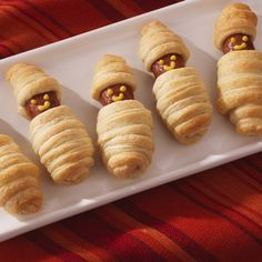 Sausages wrapped in buttery crescent rolls are a delicious finger food that's easy to make in minutes. These little mummies are great for a Halloween kids party or anytime.