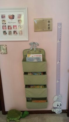 Over the door organizer + ribbon + nail= easy, accessible, and cheap bookshelf for nursery or kids room