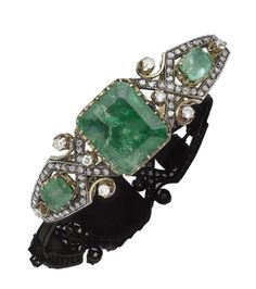 An emerald and diamond hinged bangle Set to the front with three graduated step-cut treated emeralds, within an openwork surround of geometric design set throughout cushion-shaped, brilliant and rose-cut diamonds, cushion-shaped and brilliant-cut diamonds approx. 0.55ct total, inner diameter 6.0cm