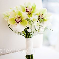 ivory bouquet of roses with white dendrobium orchids, green cymbidium orchids, and bear grass for subtle color