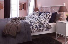 Dvojposteľ a príručné stolíky. Závesy, koberec, tienidlá a posteľné obliečky IKEA v tmavých farbách.