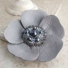 MISTY MORN  Signature Leather Flower Brooch by Viridian  ~~~*~~~    Viridians flower pins are made with an intriguing textural contrast of sparkling beads and supple leathers, for a unique accessory that can be used in a multitude of ways.    This pale cloud-gray flower has been crafted from a textured leather, with a subtle pearl glaze surrounding the beadwork. Each petal is handcut and individually stitched to a sturdy leather backing, so the flower takes on a realistic 3-D shape. In the…