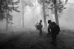 Photograph by Jake Niece, National Geographic Your Shot  Members of a hotshot crew take a break from digging a fire line on July 5. These lines must be four feet (1.2 meters) wide and deep enough that there is no longer any vegetation, explains Thiessen, National Geographic staff photographer.  If a fire is low enough, crews can dig right next to the fire, the photographer explained. If that's not possible, then crews will dig their line, then burn everything back to the active blaze.
