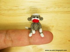 It's a teeny tiny crochet sock monkey! Crocheted with embroidery thread, it sits just one inch tall. TOO MUCH CUTE!