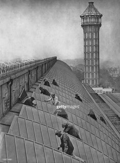 A group of men spring cleaning the glass roof of Crystal Palace in London, England in March 1930.