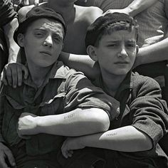 Jewish children rescued from Auschwitz show their tattoos on board the refugee immigration ship Mataroa at Haifa port, in what would later become the State of Israel, on July 15, 1945.
