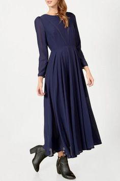 Classic and feminine navy maxi dress featuring long sleeves (to mid forearm), open v-neck back with satin trim, and full lining. Wear with gladiator sandals, delicate gold jewelry, and a bright clutch for a look that is date night and wedding-ready.