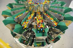 A scale measures out the correct portions of peanut M&M's before they are bagged. The factory produces 39 million individual peanut M&M's daily.