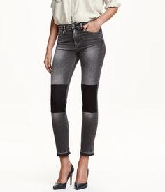 Ankle-length, 5-pocket jeans in washed stretch denim with distressed details. Regular waist, slim legs, and raw-edge hems. Darker areas on knees with look of removed patches.