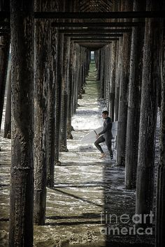 A surfer passes under the pier in Oceanside California. To view or purchase my prints, visit joan-carroll.artistwebsites.com THANKS!