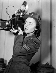 Sergeant Karen M. Hermiston of the Canadian WOmen's Army Corps (C.W.A.C.), who is holding an Anniversary Speed Graphic camera, London, England, 15 November 1945.