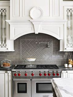 Gray porcelain subway tiles create drama against pure white cabinetry. Behind the range, a herringbone-pattern inset on the backsplash breaks up the backsplash and adds another focal point to the wall.