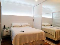A porta do armário recebeu um espelho grande, que dá a chance de aumentar visualmente o espaço do quarto